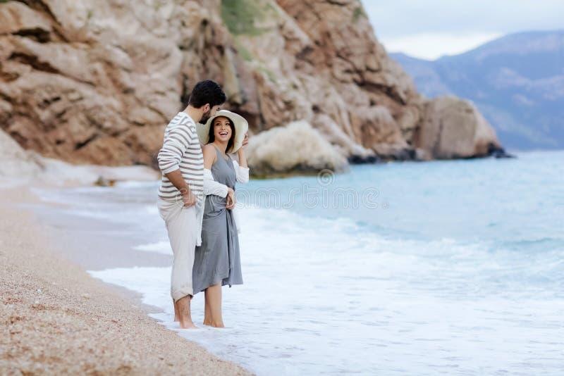 爱的一起享用在海附近的一名男人和妇女,由海滩负责,笑,亲吻 库存照片