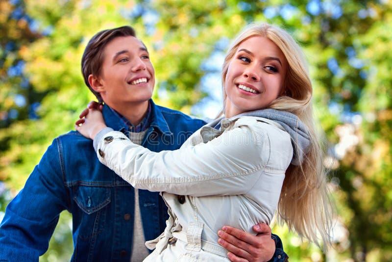 爱的人在秋天公园保留女孩他的胳膊 免版税库存图片