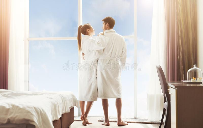 爱的夫妇在酒店房间,站立在窗口附近 免版税库存照片