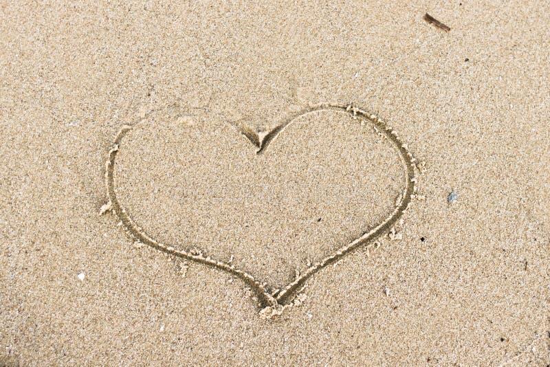 爱的标志以心脏的形式在沙子 免版税库存照片