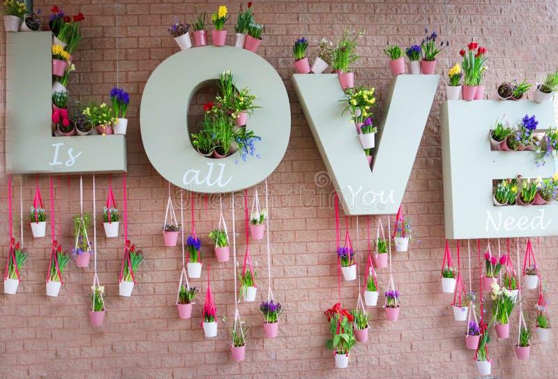 爱的浪漫标志与花和与桃红色砖在背景中 免版税库存图片
