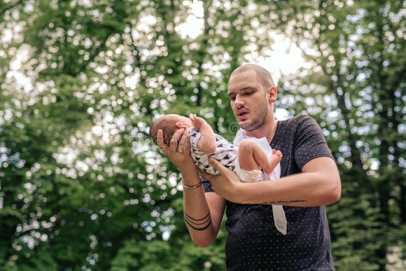 爱的父亲在他的手上的生长他的男婴外面 免版税图库摄影