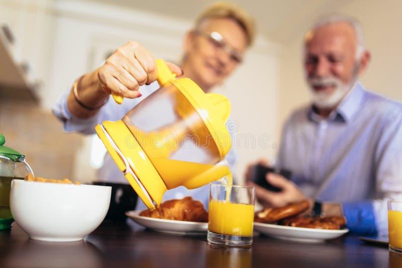 爱的资深夫妇获得准备在早餐的乐趣健康食品在厨房 图库摄影
