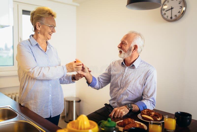 爱的资深夫妇获得准备在早餐的乐趣健康食品在厨房 免版税库存图片