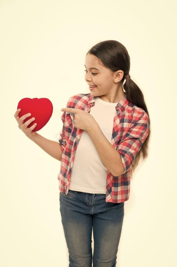 爱的逗人喜爱的女孩 把手指指向的女孩红心 表现出的小孩爱在情人节 ? 免版税库存图片