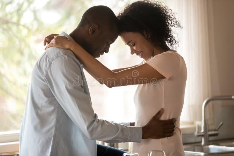 爱着双种族的丈夫和妻子抚摸前额享受约会 免版税库存照片