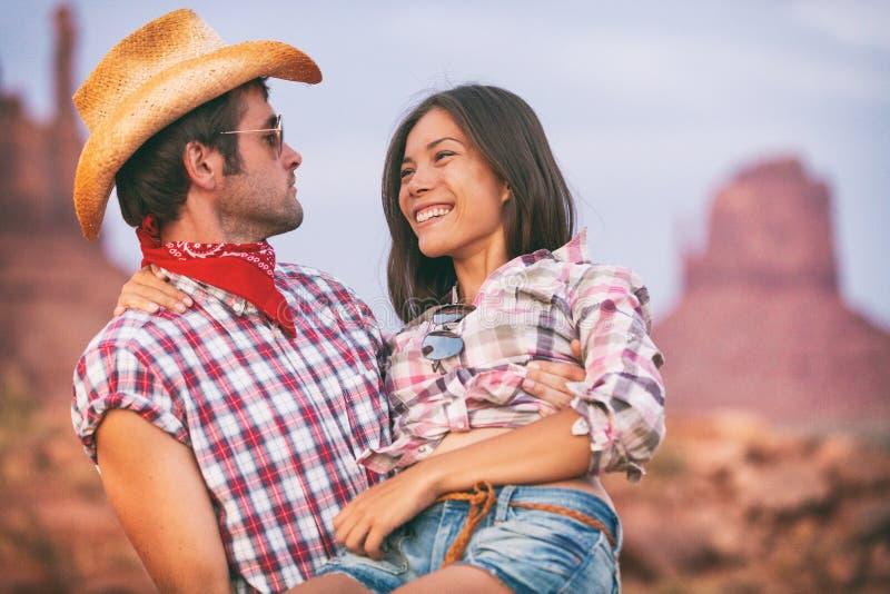 爱逗人喜爱的夫妇的恋人牛仔和女牛仔在美国backcountry风景 运载亚裔女朋友的男朋友佩带的牛仔帽 免版税库存照片