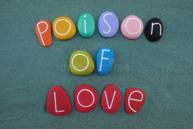 爱,创造性的文本毒物组成与在绿色沙子的多色的石头 免版税库存照片