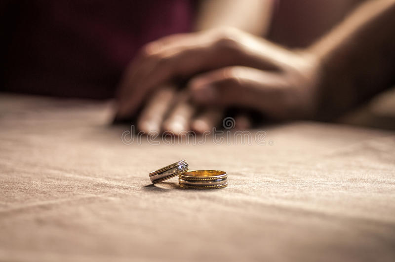 爱,华伦泰` s天和婚礼概念 两个婚戒用在背景中弄脏的男人和妇女手 选择聚焦 免版税库存照片