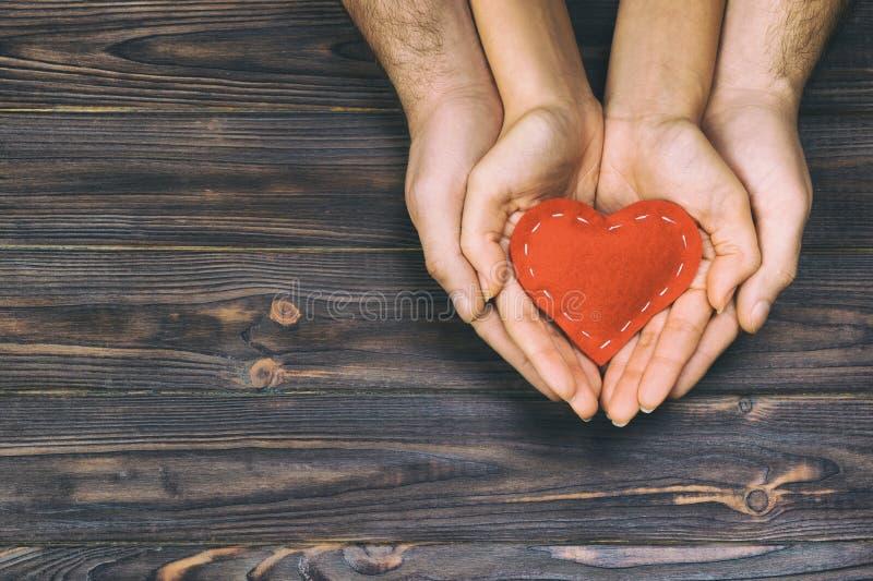 爱,家庭观念 关闭拿着红色橡胶心脏的男人和妇女手一起被定调子,葡萄酒 免版税库存照片