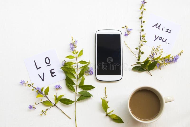 爱,想念您消息与手机,热的咖啡的卡片手写 免版税库存图片