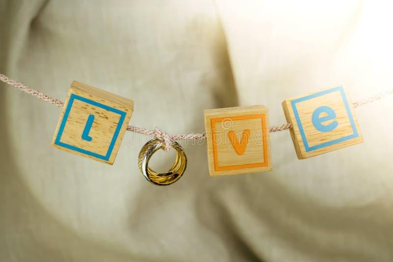 爱从垂悬在绳索的金戒指和小木立方体的词 免版税库存照片