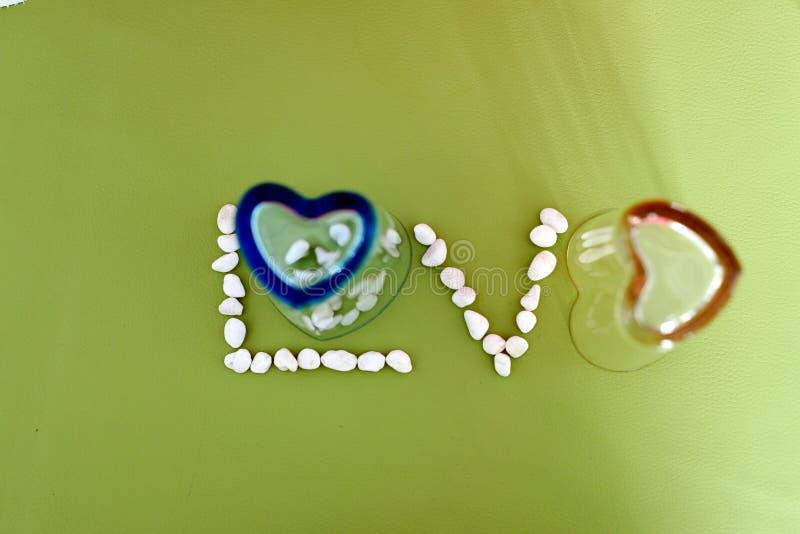 爱从心脏形状玻璃和一点石头的文本 免版税库存图片