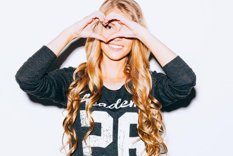 爱 有长的blon头发的特写镜头画象微笑的愉快的少妇,做心脏标志,标志有手白色墙壁背景 库存图片