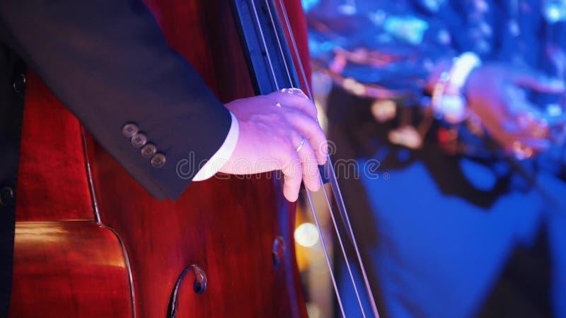 爵士乐音乐会在音乐厅里 弹大提琴的服装的一个人 免版税库存照片