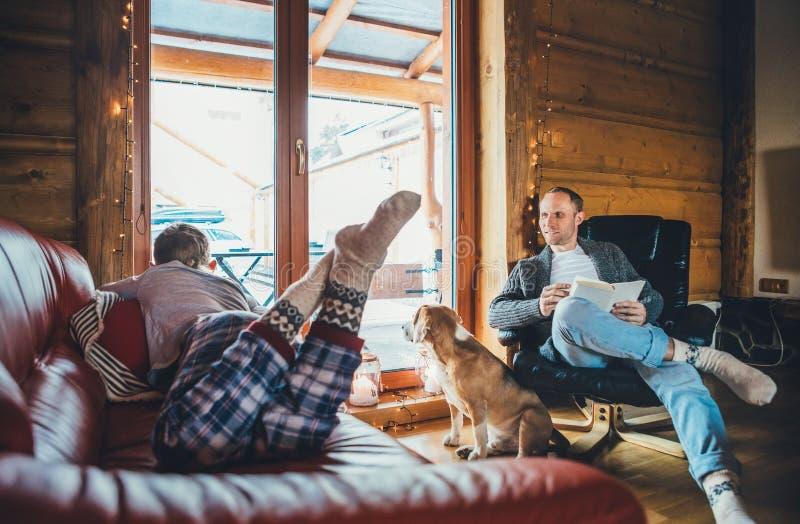 父亲、儿子和他的小猎犬狗消费假日时间在舒适乡间别墅里 读书,男孩的爸爸说谎和听,狗 免版税库存图片
