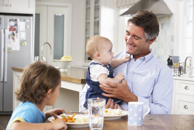 父亲、儿子和小女儿有膳食在厨房一起 库存图片