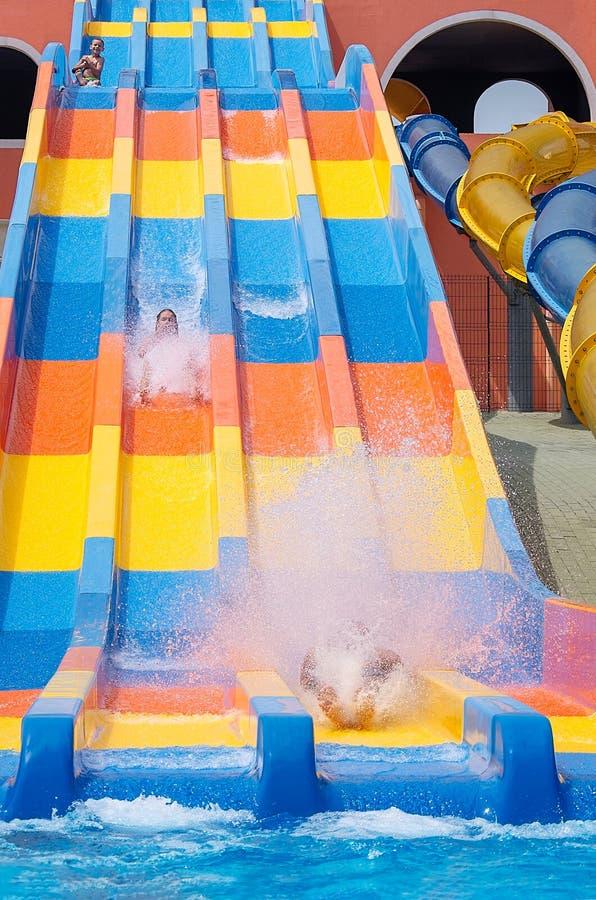 父亲、女儿和儿子获得乐趣在去下来在水滑道的水色公园 免版税库存图片