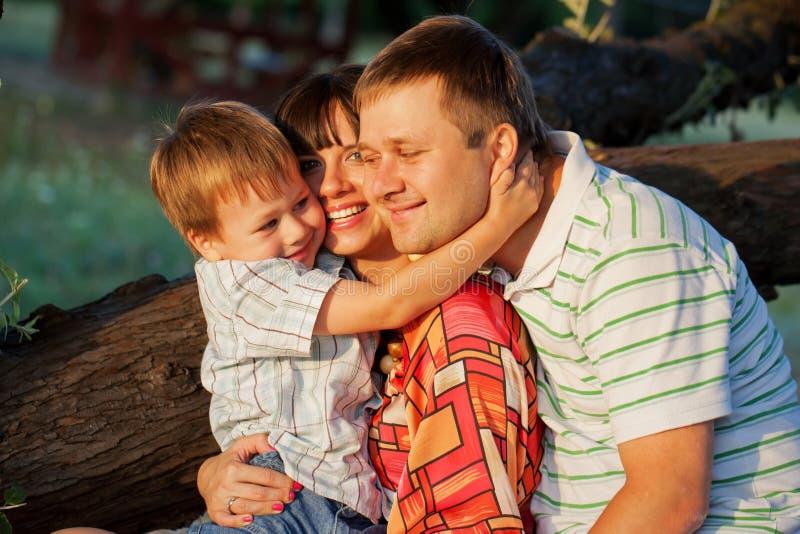 父亲、母亲和儿子拥抱 库存图片