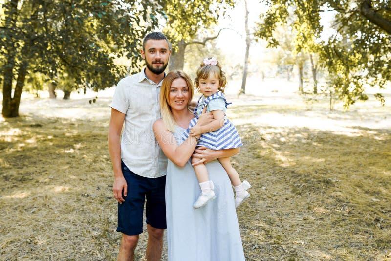 父亲、母亲和女儿在公园 友好的家庭 r 库存图片