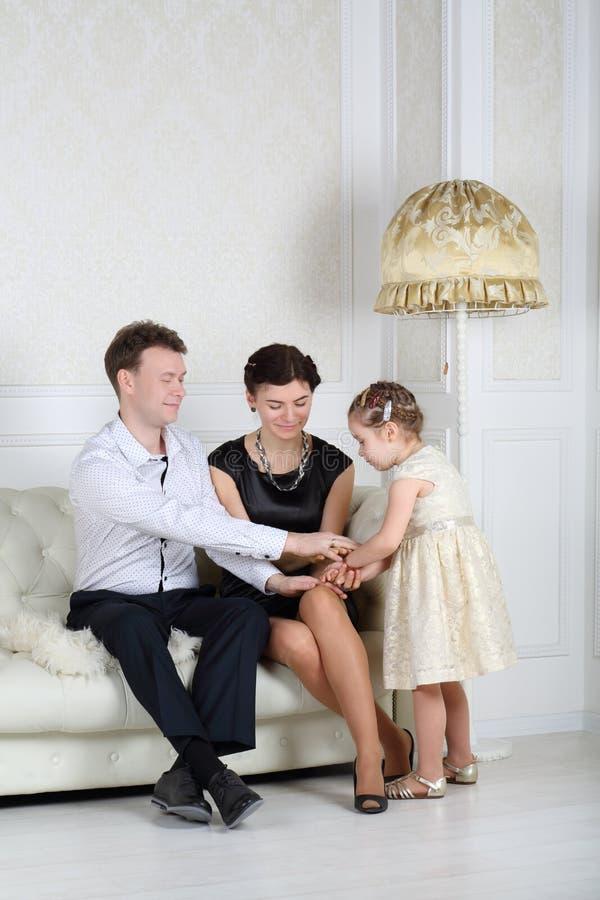 父亲、母亲和小逗人喜爱的女儿握手 免版税库存图片
