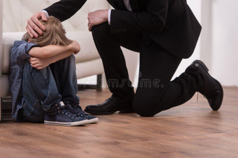 父亲下跪和舒适哀伤的孩子 免版税库存图片