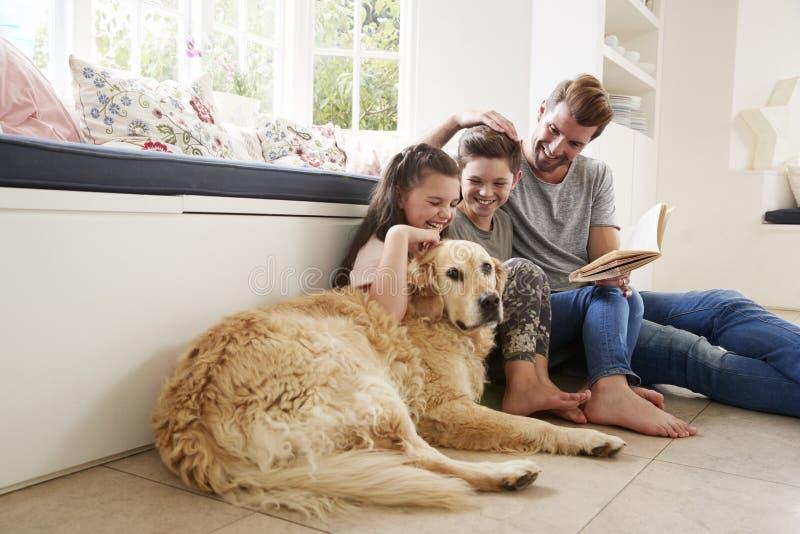 父亲与儿子和女儿和爱犬的阅读书在家 免版税图库摄影