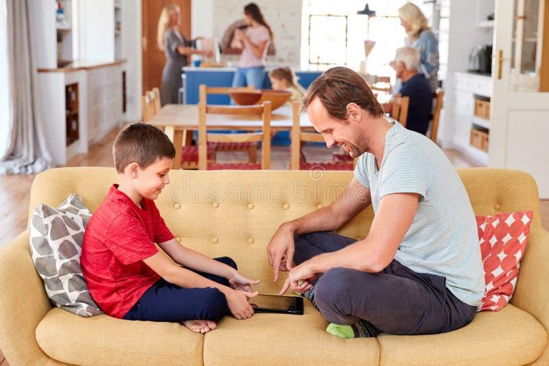 父亲与儿子在家打比赛的沙发坐数字片剂 免版税库存照片