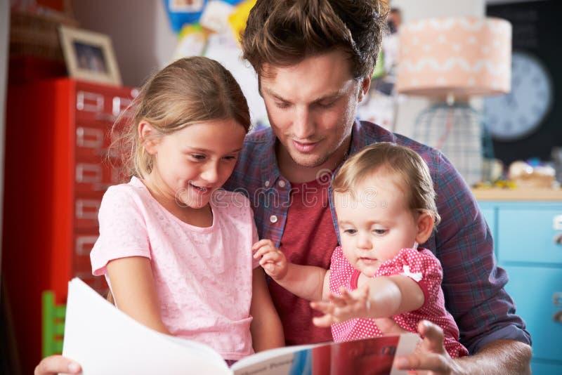 父亲与女儿的阅读书在卧室 免版税库存图片