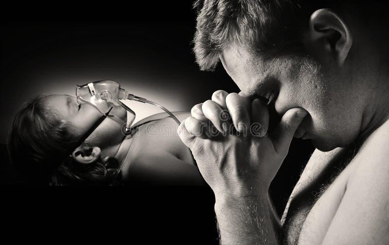 父亲为不适的女儿健康祈祷 免版税库存图片