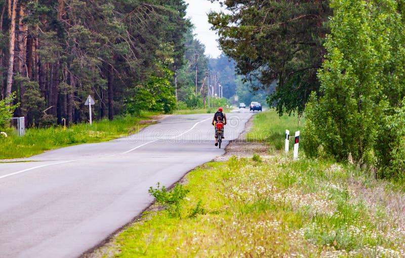 父亲乘在高速公路的自行车运载女儿 免版税库存图片