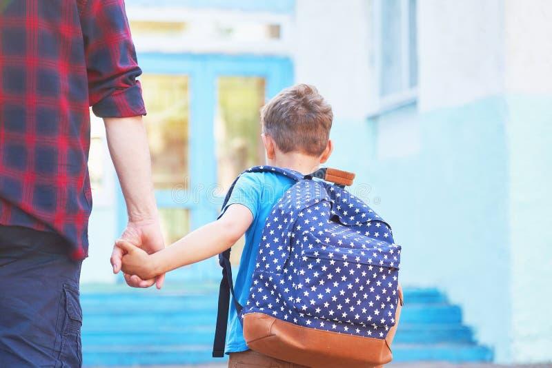 父亲伴随孩子到学校 有从后面去除的孩子的一个人 握她的儿子的手的溺爱的爸爸去 免版税库存照片