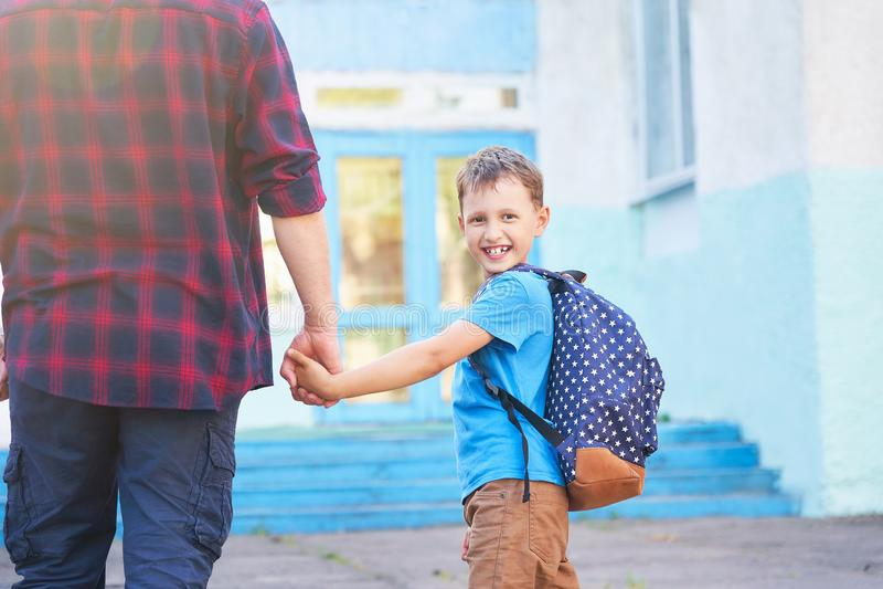 父亲伴随孩子到学校 有从后面去除的孩子的一个人 握她的儿子的手的溺爱的爸爸去 库存照片