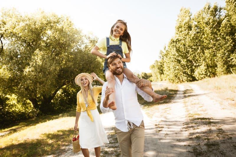 父亲使用与女儿的,女孩坐他的肩膀 免版税库存照片