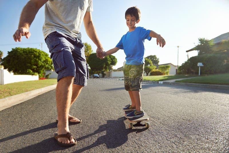 父亲儿子滑板 免版税库存图片