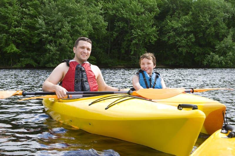 父亲划皮船的儿子 图库摄影