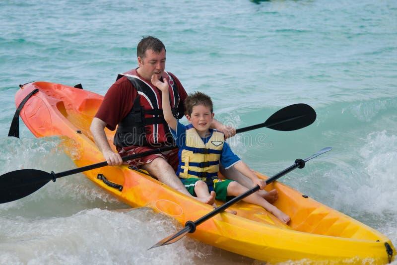 父亲划皮船的儿子 免版税图库摄影