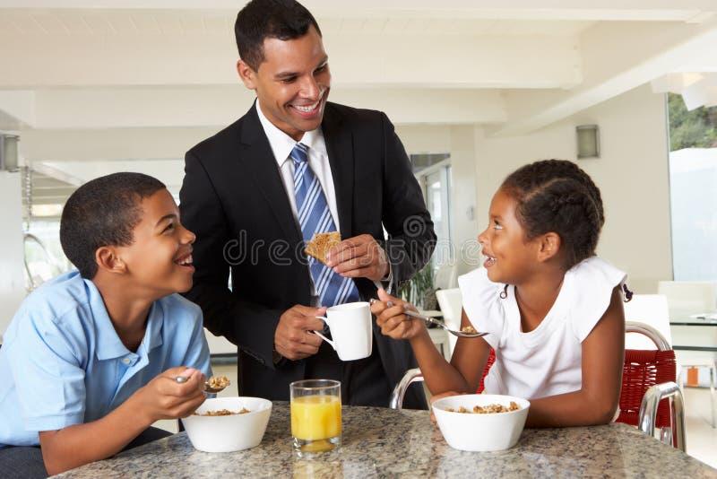父亲吃与孩子的早餐在工作前 库存照片