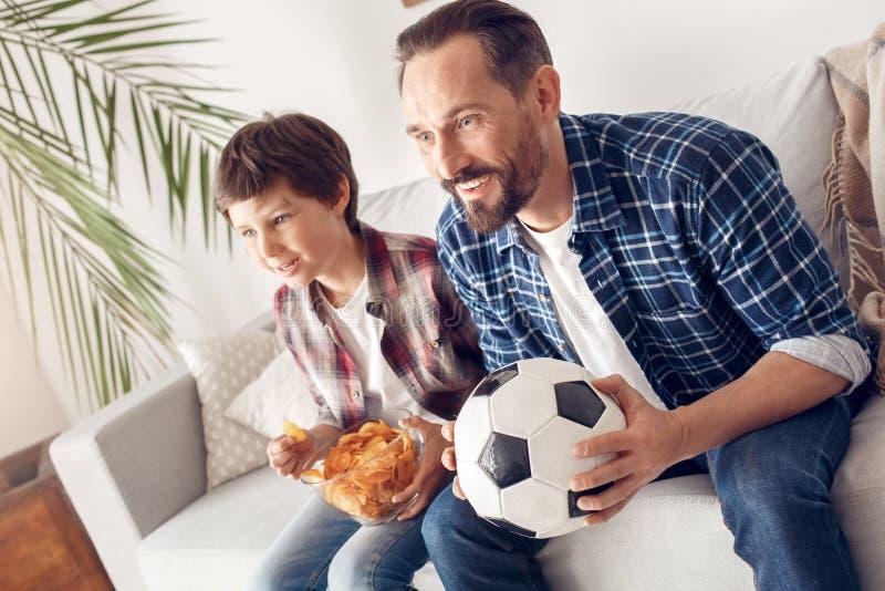 父亲和一点儿子在家坐吃薯片观看的足球比赛的沙发男孩与爸爸藏品一起 库存图片