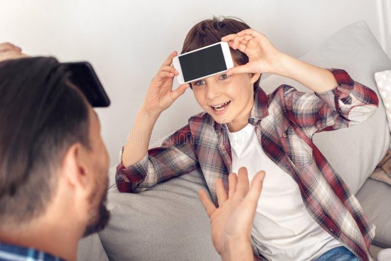 父亲和一点儿子在家坐夸大头的沙发与智能手机看爸爸的男孩特写镜头激动 免版税图库摄影