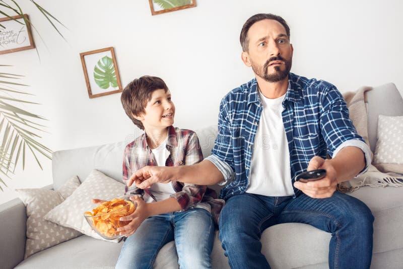 父亲和一点儿子在家坐沙发男孩藏品土豆船快乐的看的爸爸观看的橄榄球 库存图片