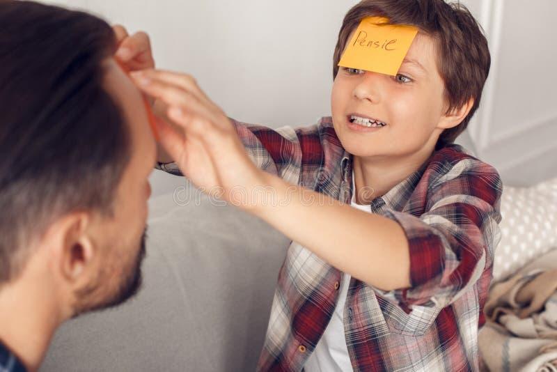 父亲和一点儿子在家坐演奏前额侦探男孩的沙发黏附纸对爸爸的顶头激动的关闭 免版税库存照片