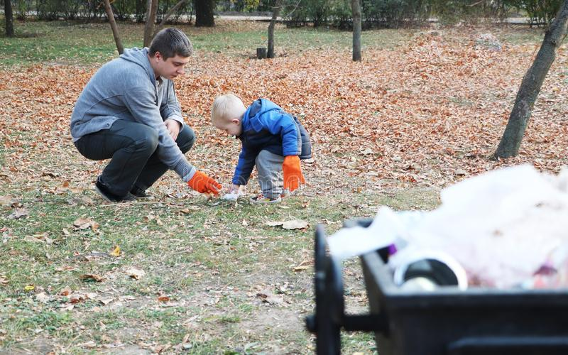 父亲和一点儿子换气在公园 背景-垃圾和垃圾桶 生态和保护行星的概念 免版税图库摄影