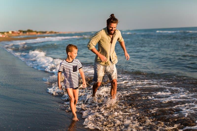 父亲和儿子、人&男孩孩子,跑和获得乐趣在一个晴朗的海滩的沙子和波浪 免版税库存照片