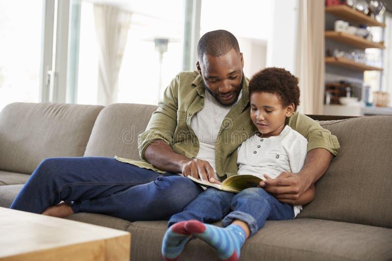 父亲和儿子一起坐在休息室阅读书的沙发 免版税库存图片