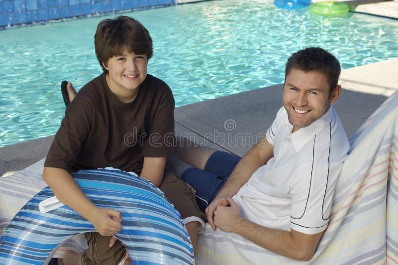 父亲和儿子一起坐Deckchair 库存照片