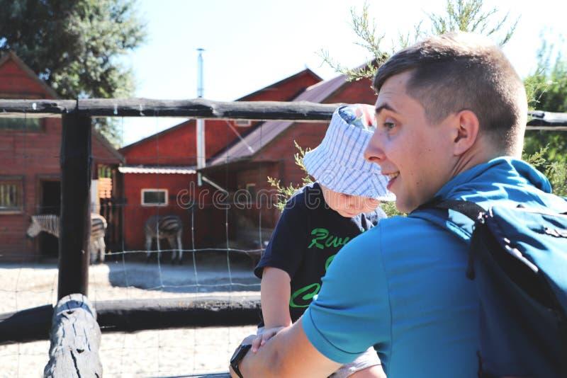 父亲和儿子一起家庭时间在动物园里 免版税库存图片