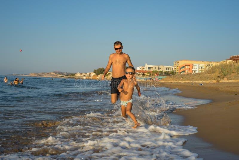 父亲和儿子一起跑在海滩的4-5,有质量家庭时间 美国 日落 美好的夏天好日子,蓝色海 免版税库存图片