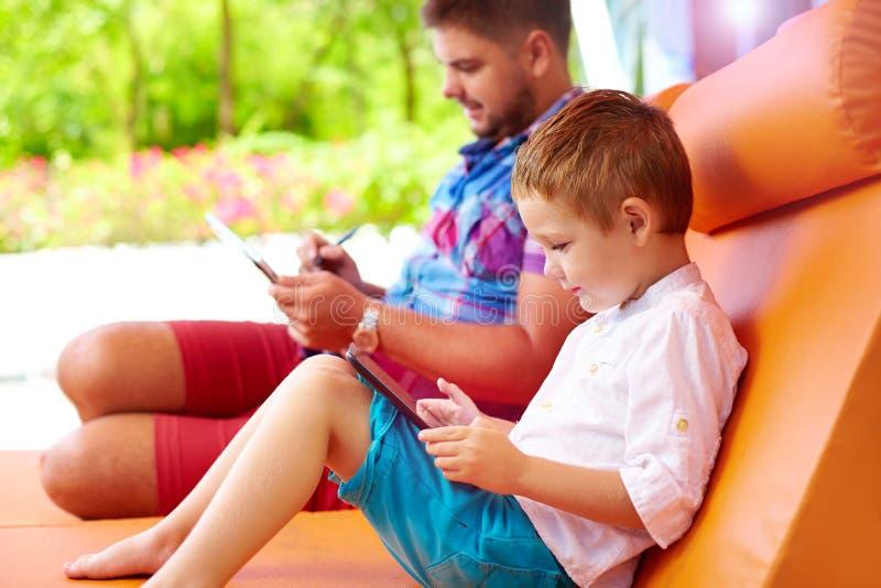 父亲和儿子冲浪的网通过片剂,在假期时 库存照片