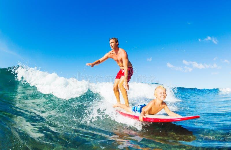父亲和儿子冲浪 库存图片